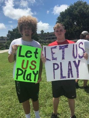 Peyton Mainolfi, left, and Dominic Janiszewski, right, hold signs outside of the Palm Beach County School District on Thursday during a protest they helped organize, to allow student-athletes to practice and play fall sports.