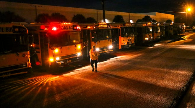 A driver heads to her bus before dawn at the Palm Beach County School District's facility in Riviera Beach in 2015. (Lannis Waters / The Palm Beach Post)
