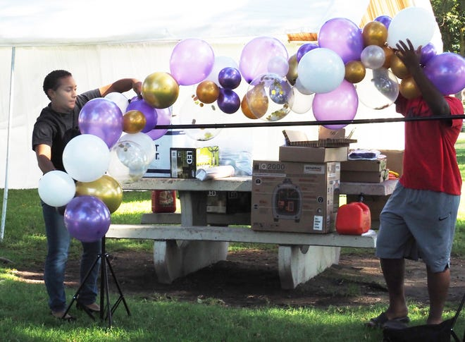 Rose Langley, left, helps decorate with balloons for a memorial at Victory Park for Vernita Lymuel, a longtime Stockton Unified employee and African-American Athletes Hall of Fame inductee who died July 27 from COVID-19.