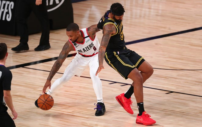 Portland Trail Blazers guard Damian Lillard (0) steals the ball from Los Angeles Lakers forward Markieff Morris, right, in the second half of Game 4 of an NBA basketball first-round playoff series, Monday, Aug. 24, 2020, in Lake Buena Vista, Fla. (Kim Klement/Pool Photo via AP)