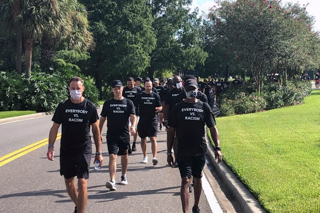 NBA referees march in support of players seeking an end to racial injustice in Lake Buena Vista on Thursday. Their march came shortly before players met to decide on restarting the season after three games were postponed Wednesday. Racial injustice was part of the discussion at Florida's football practice Thursday.