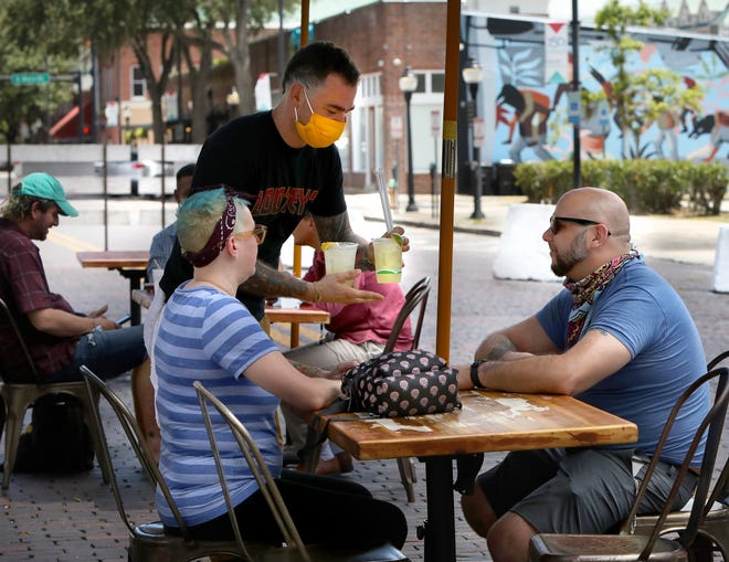 Server Timothy Hutchens, from Loosey's Downtown, bring a couple drinks to Melanie Kelly, left and her husband Cyrus Maradiajam during lunch in the outdoor dining area on SW 1st Ave. outside of Loosey's Downtown, in Gainesville, Fla. Aug. 26, 2020. The Gainesville City Commission voted this week to repeal the city's open container laws.