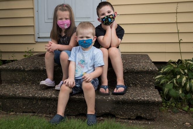 Siblings Margot, 4, Clive, 2, and Harry Ruesch, 7, sit on the front steps sporting their bests masks on Thursday  at their home in Wisconsin Rapids. Their mother, Heather Ruesch, says her efforts to acclimate the children to mask wearing have gotten to the point where her kids will wear masks around the house just because they like them.
