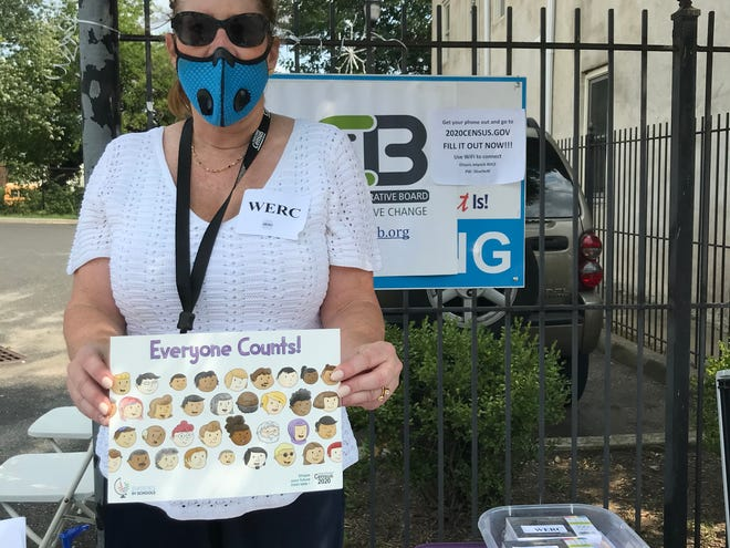 Rita Weber of Workforce and Economic Revitalization for Communities (WERC) holds up a coloring book that was given away, along with backpacks, masks, notebooks and ice cream, as a group of Camden nonprofits teamed up to encourage people to be counted in the U.S. Census.