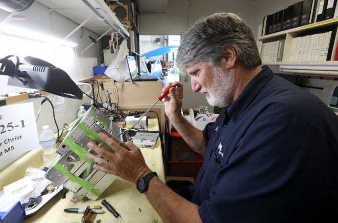 Jim Newman works on communication equipment for a plane undergoing repair at MMS Aviation in Coshocton. After extensive travels, Newman is now a training supervisor specializing in aircraft avionics (electronics) at MMS.