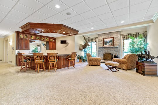 A lower level bar and entertainment area of this home at 1576 Kirkway Road in Bloomfield Hills. It is a very large and lavish brick home in a posh neighborhood with six full bedroom suites, two kitchens, elevator, handsome brickwork and heated garage space for seven cars.