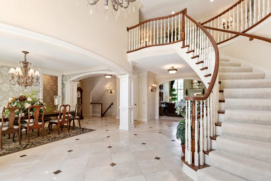 Curving staircase floats without support next to the foyer and the dining room. The rooms here have gently arched entrances, supported by embellished columns. Main level floors are white honed marble.