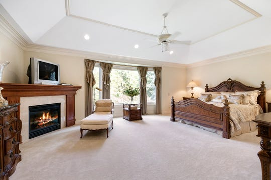 The owners' suite is one of many rooms with an elaborate ceiling -- here a tray ceiling that's stepped, plus thick crown molding. This bedroom fireplace is fully gas. There are four more fireplaces that all burn wood, but are prepped with gas lines