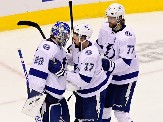 Teammates Tampa Bay Lightning goaltender Andrei Vasilevskiy (88) and teammates Alex Killorn (17) and Victor Hedman (77) celebrate a 7-1 win over the Boston Bruins in Game 3 of an NHL hockey second-round playoff series, Wednesday, Aug. 26, 2020, in Toronto.