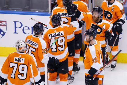 Philadelphia Flyers right wing Jakub Voracek (93) high fives teammates as they leave the ice following their overtime victory in an NHL Stanley Cup Eastern Conference playoff hockey game against the New York Islanders in Toronto, Ontario,  Wednesday, Aug. 26, 2020.