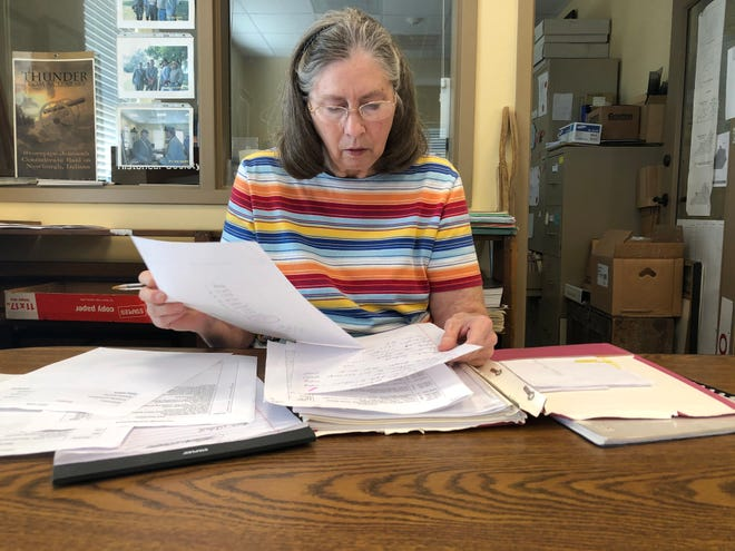 Linda Hallmark, longtime vice president of the Henderson County Genealogical and Historical Society, reviews an inventory of historical artifacts on hand at the society's office at the Depot at 101 N. Water St. and on display in the adjacent Depot Community Room. The society is preparing to disband and is turning over its collection of materials to the Henderson County Public Library. (Photo by Chuck Stinnett)