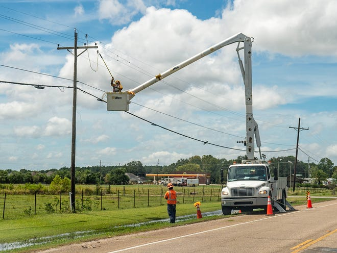 Linemen with Altec work on downed powerlines along U.S. Highway 90 Thursday, Aug. 27, 2020. Editor's note: The injured lineman is not pictured here.