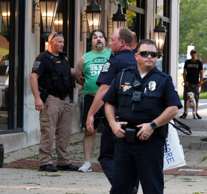 William Rotkis, in green, is detained by members of local law enforcement after he allegedly assaulted a Lancaster resident during a protest Wednesday, Aug. 26. Rotkis was charged with assault, a first-degree misdemeanor, and failure to cease and desist, a fourth-degree misdemeanor.