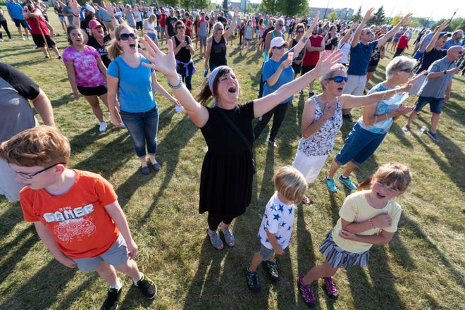 A woman sings during an ecumenical prayer service put on by multiple congregations Thursday in Kenosha. About 1,000 people attended. The pastors, who meet regularly for private prayer, decided to hold a public event to encourage residents to pray for the city.