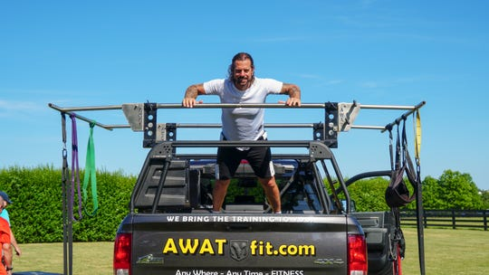 Richard Decker, CEO and founder of AWATfit, stands on his truck, the centerpiece of his mobile gym business.