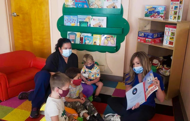 Children at Little Playmates in Las Cruces, New Mexico, wear masks as workers read to them in August 2020.