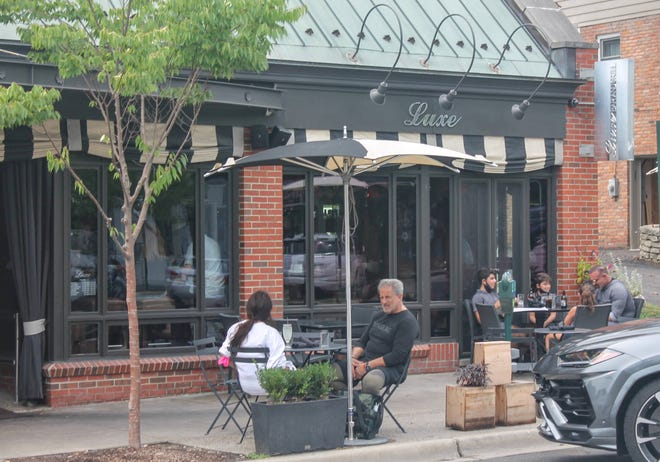 Diners eat outside of Luxe Bar and Grill Aug. 26, 2020 in Birmingham. The restaurant has proposed expanding into the space to the south of the bar and expand outdoor seating.