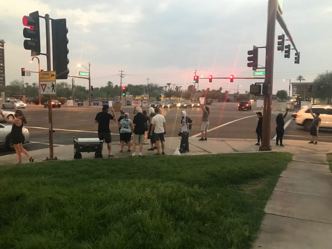 A handful of protesters wait on the corner of Camelback Road and Central Avenue after a march there was canceled due to threats against organizers on Aug. 26, 2020.