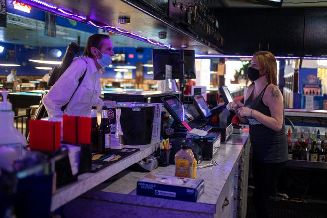 Even after the governor's order lifting restrictions went public on Thursday, patrons of Bull Shooters pool hall and sports bar in west Phoenix were still coming wearing masks, owner Mike Bates said.