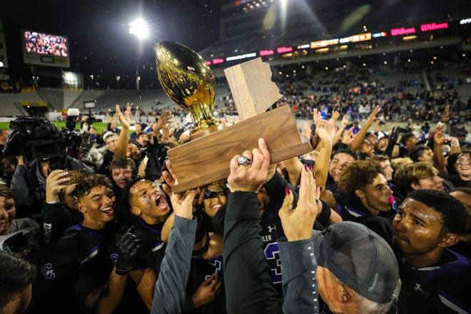 Chandler hoists the trophy after beating Saguaro in the Open Division State Championship on Dec. 7, 2019, in Tempe.