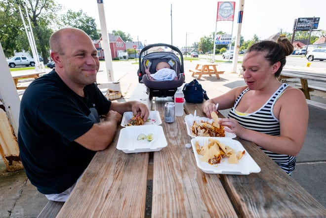 Annie and Sean Richardson enjoy tacos and a wet burrito from El Hombre Grande while their 4-month-old son David rests Thursday, Aug. 27, 2020, at the former Admiral station in Port Huron. Huron Food Fleet will no longer be located at the gas station due to a limited number of tenants available at the property at one time and a lack of foot traffic.