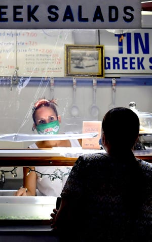 Tina's Greek Salads employee Michelle Grove takes an order from a customer at the Central Market stand Thursday, August, 27, 2020. She and her mother, Cindy McCoury, have worked there for 30 years. It was the last day operation for the 35-year-old business. Bill Kalina photo