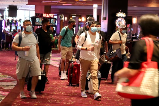 Visitors roll their bags toward their rooms at the Mirage on Aug. 27, 2020.
