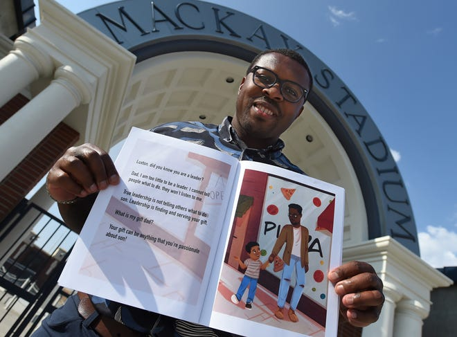 Former Wolf Pack running back Stefphon Jefferson shows the children's book he wrote as he stands in front the Mackay Stadium entrance on Wednesday.