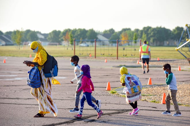 A family crosses the playground to drop the children off for their first day of school on Thursday, August 27, at Discovery Elementary School in Sioux Falls.