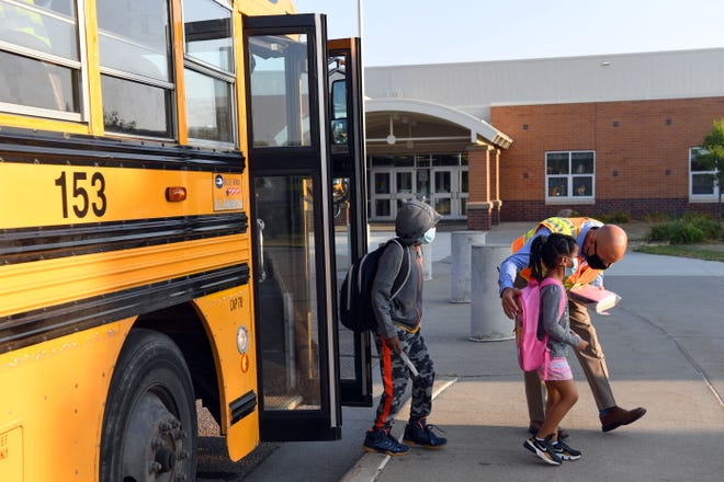 Principal Daniel Fischer greets students as they arrive off the bus for the first day of school on Thursday, August 27, at Discovery Elementary School in Sioux Falls.