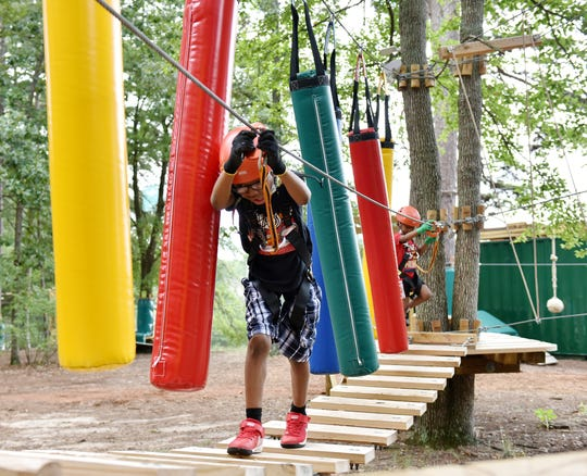 Justin Searcy, 8, walks on a bridge in a course at Treetop Quest in Greenville.