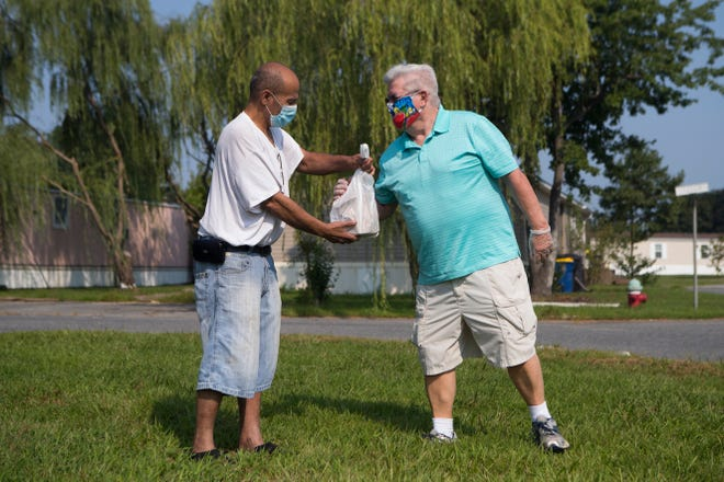 Meals on Wheels volunteer Bob Casey, right, delivers a meal to a recipient Thursday, August 27, 2020, in Dover.