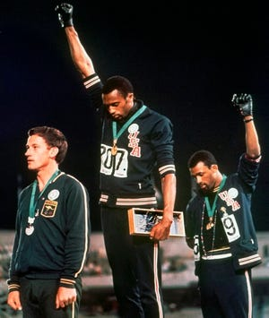 John Carlos (right) and Tommie Smith stare downward and extend gloved hands skyward in a Black Power salute at the 1968 Summer Olympics.