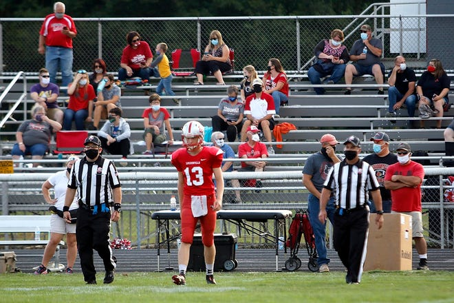 Loudonville High School's Logan Huffman (13) walks out to midfield with the officials for the coin toss before the game against Triway High School during the first game of the high school football season at Loudonville High School Thursday, Aug. 27, 2020.