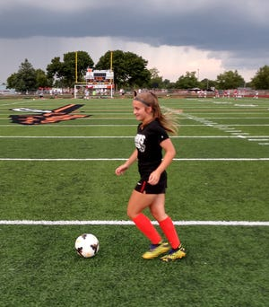 Ashland High's Gracie Fussner warms up before her team's game against Madison Thursday night at Community Stadium.