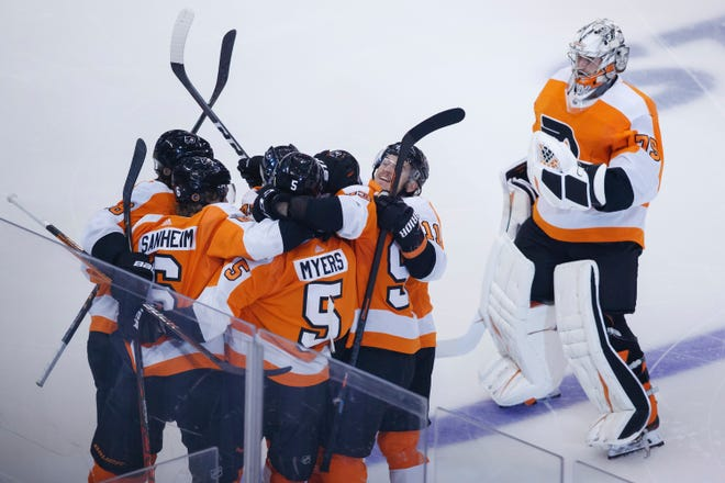 Flyers defenseman Phil Myers, 5, is embraced by teammates as he celebrates his game-winning goal in overtime during Game 2 against the Islanders.