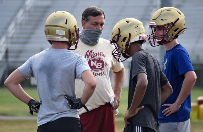New Brighton head coach Joe Greco wears a mask as he speaks to players during practice.