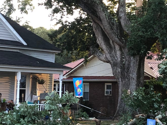 A tree limb snapped off the large tree overlooking this house at 915 Sunset Avenue Friday, leading to a power outage in the city.