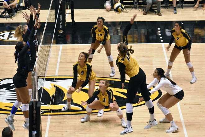A group of Missouri players surrond outside hitter Kylie Deberg (12) as she spikes the ball during a Southeastern Conference match against Kentucky last season.