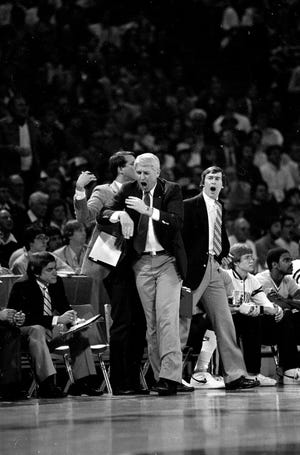 Iowa head coach Lute Olson, center, and his assistant coaches leap off the bench in disbelief after the referees failed to call traveling against Villanova during Friday night's NCAA Midwest Regional semifinal game in Kansas City, Mo., on March 25, 1983.