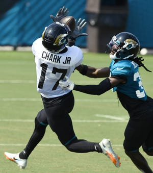 Jaguars WR #17, DJ Chark Jr. pulls in an over the shoulder pass while being defended by CB #37, Tre Herndon as the Jacksonville Jaguars went through drills in pads for the first time during training camp at the practice fields outside TIAA Bank Field Monday, August 17, 2020. [Bob Self/Florida Times-Union]