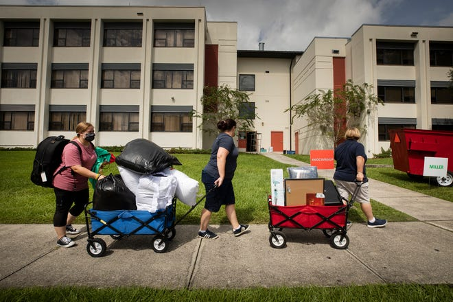 Barabara Miraglia, right, and Cassandra Currier, center, help transport their daughter Mia Currier Miraglia, left, and her belongings into Hollis Dorm during move-in day at Florida Southern College in Lakeland at the beginning of the fall term.