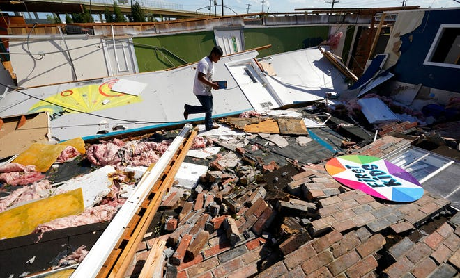 Benjamin Luna helps recover items from the children's wing of the First Pentecostal Church that was destroyed by Hurricane Laura, Thursday, Aug. 27, 2020, in Orange, Texas.