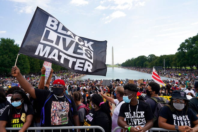 "People attend the March on Washington Friday in Washington, on the 57th anniversary of the Rev. Martin Luther King Jr.'s ""I Have A Dream"" speech."