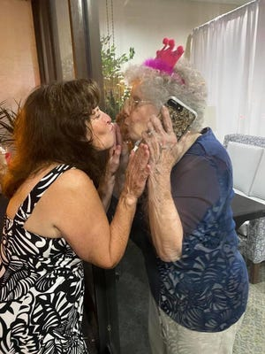Cindy Snow Ferre, left, kisses her mother, Peggy Chatham Snow, through the glass of a Lake Morton Plaza window Thursday night as they celebrated Snow's 90th birthday.