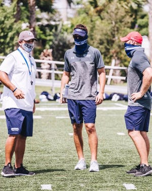 Members of the Keiser coaching staff can be seen in masks while the team practices during a Saturday scrimmage.