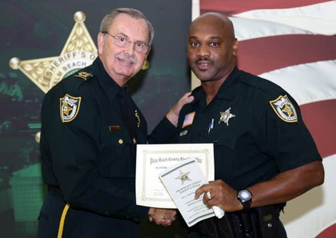 Corrections Deputy Maurice Ford shakes hands with Palm Beach County Sheriff Ric Bradshaw in an undated photo. Ford, 50, is the second deputy to die from the coronavirus this year, the sheriff's office announced Thursday, August 28, 2020. [Photo provided by the Palm Beach County Sheriff's Office]