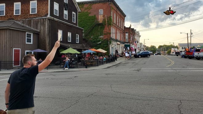 Jay D Smith, of the band The Living Birds, preaches to both sides of the street Aug. 27 in downtown Garrettsville. Black lives Matter demonstrators, and diners at Garrett's Mill, are on one side, while a group of counter-protesters are on the other side.