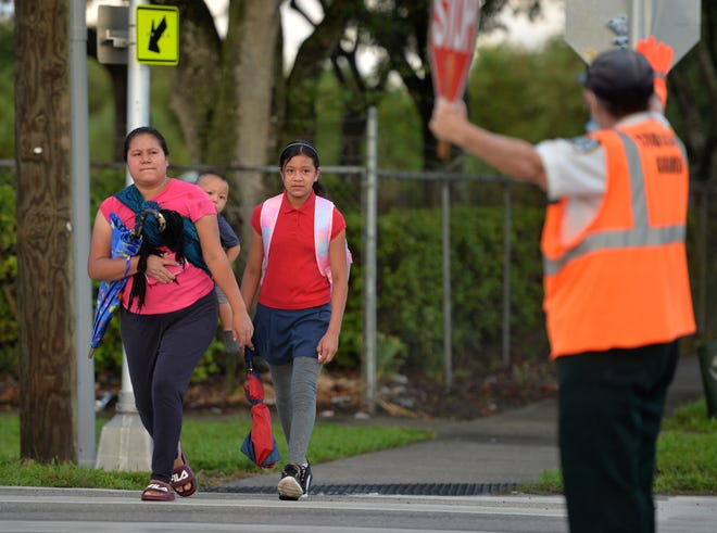 Samoset Elementary School fourth-grader Flordaly Lopez,10, walks to school with her mother, Avely, and brother David on the first day of classes for students in Manatee County on Aug. 17.