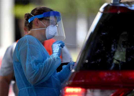 Florida Department of Health nurse Maureen McCarron prepares to collect a throat culture from a driver in June 2020 at the Englewood Sports Complex in Sarasota County.